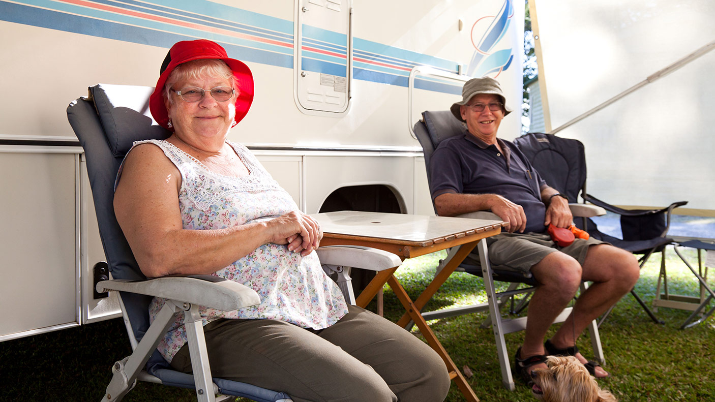 Two people sitting in front of their caravan