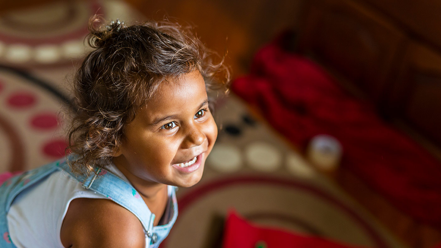 Happy Young Australian Aboriginal Girl Learning to Sing and Dance to a Song - stock photo