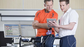 A sports scientist showing an athlete some results on a tablet