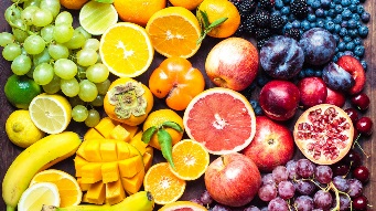 A colourful spectrum of fruit: oranges, lemons, limes, mandarins, grapes, plums, grapefruit, pomegranate, persimmons, bananas, cherries, apples, mangoes, blackberries and blueberries.
